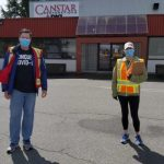 Two volunteers on the road wearing mask